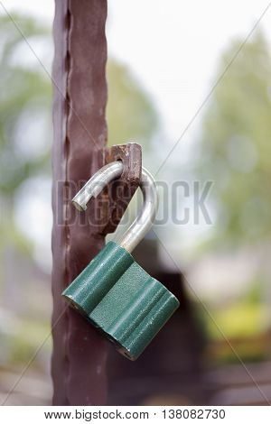 Close view of a green lock on a metallic gate
