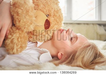 beautiful blond girl dreaming with teddy bear