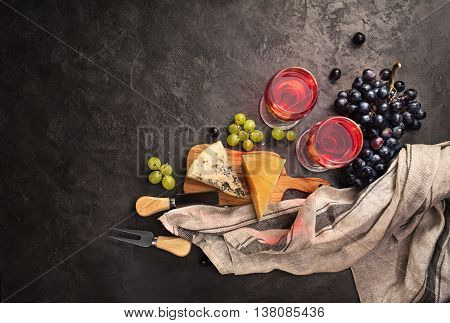 Blue cheese, parmesan, red wine and grapes on dark stone background. Food background with copy space