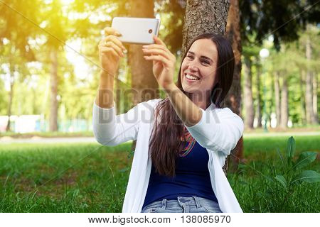 Beautiful young woman is sitting under the tree in the park and making a selfie on her smart phone