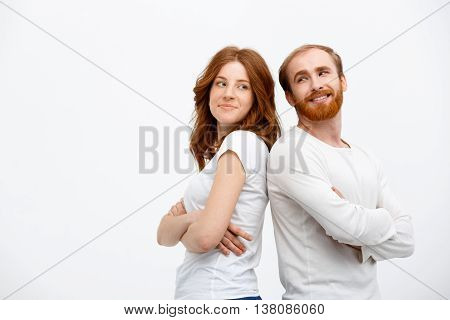 Cheerful redhead girl with boy dressed in white t-shirt  standing over white background.