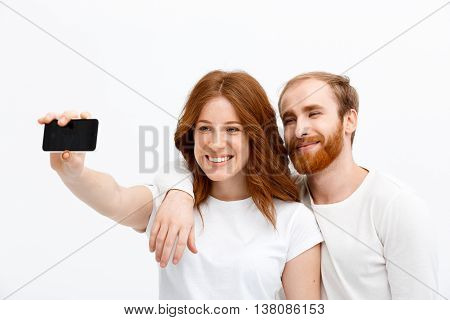 Beautiful redhead girl and boy make selfie over white background smiling