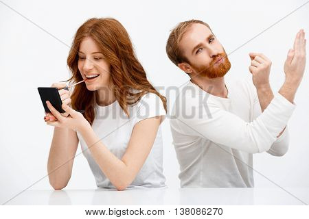 Funny redhead boy copying redhead girl putting on lip gloss over white background