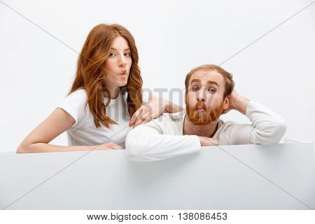Funny redhead boy and girl posing at white table being silly