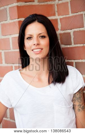 Cool young woman during a photo shoot on the street with a tatoo on arm