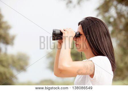 Brunette woman in the park looking through binoculars
