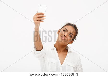 Portrait of young beautiful african girl in white blouse making selfie, smiling over white background.