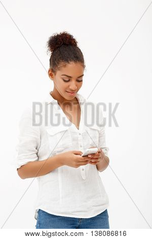 Portrait of young beautiful african girl with phone smiling, looking at phone over white background.