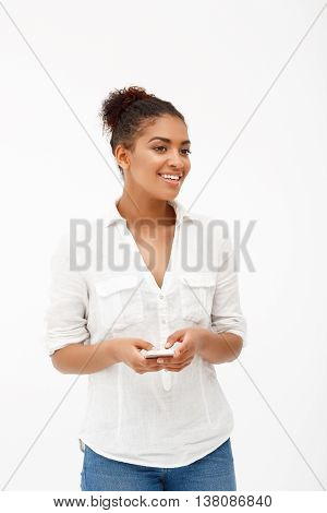Portrait of young beautiful african girl with phone smiling over white background.