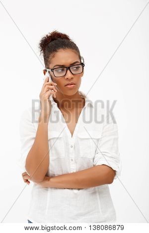 Portrait of young successful african business lady in glasses speaking on phone over white background.