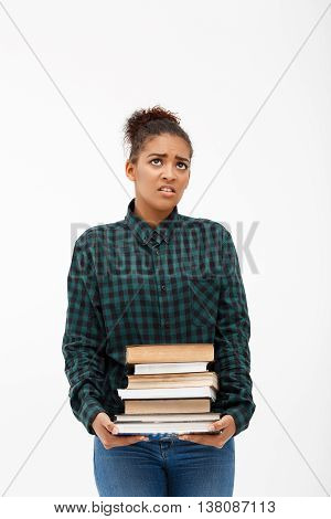 Portrait of upset young beautiful african girl in green blouse and jeans  with books over white background.