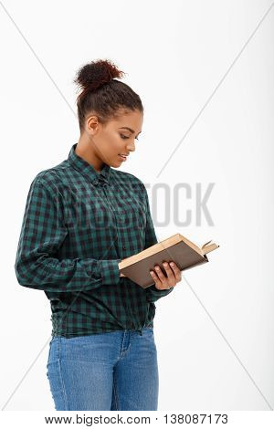 Portrait of  young beautiful african girl in green blouse and jeans reading book over white background.