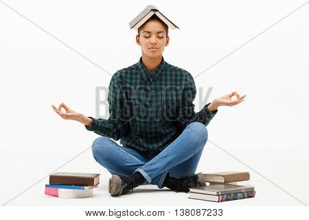 Portrait of young beautiful african girl in green blouse and jeans meditating, sitting on floor with books over white background. Copy space.