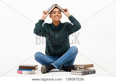 Portrait of young beautiful african girl in green blouse and jeans smiling, looking at camera, sitting on floor with books over white background. Copy space.