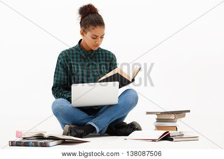 Portrait of young beautiful african girl with laptop and books reading over white background. Copy space.