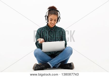 Portrait of young beautiful african girl in headphones with laptop listening music, smiling, looking at screen over white background. Copy space.