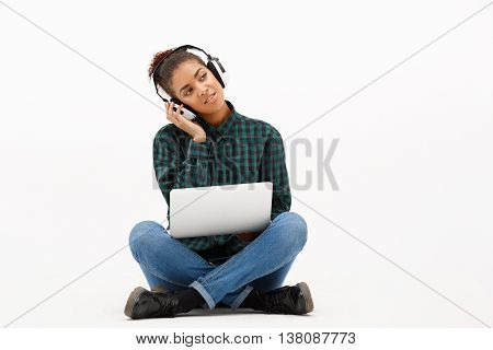 Portrait of young beautiful african girl in headphones with laptop listening music, smiling, over white background. Copy space.