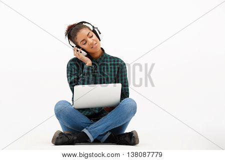 Portrait of young beautiful african girl in headphones with laptop listening music, smiling, eyes closed over white background. Copy space.