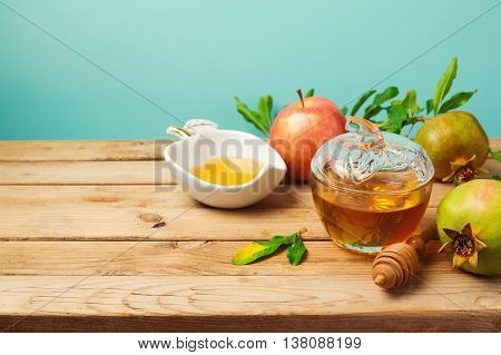 Jewish holiday Rosh Hashana background with honey jar apple and pomegranate on wooden table over mint background.