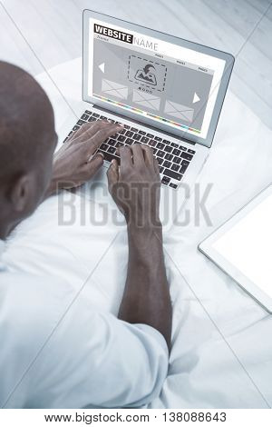Composite image of website interface against overhead view of a man using laptop