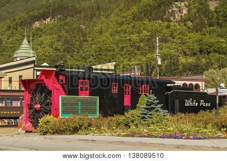 SKAGWAY ALASKA USA - JULY 12 2011: Old Snow Blower Train and Trees in the Background