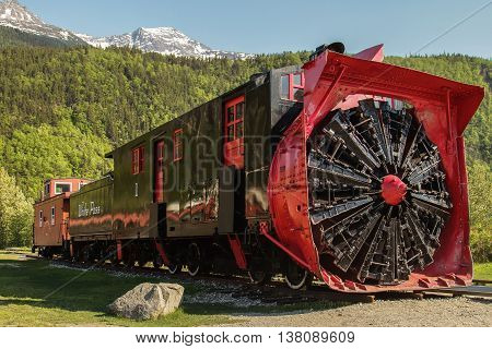 SKAGWAY ALASKA USA - MAY 31 2011: Old Snow Blower Train and Trees in the Background
