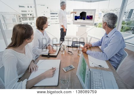 Smartphone, tablet computer and laptop against business people listening to colleagues presentation