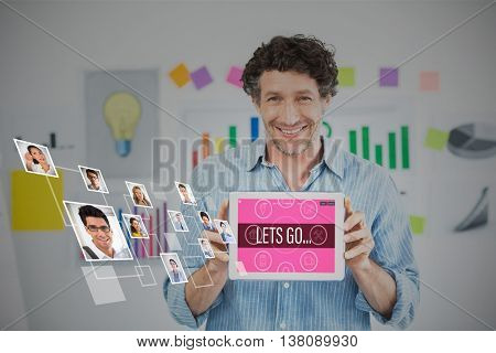 Businessman showing digital tablet with blank screen in creative office against portrait of business people