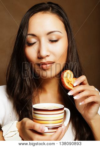 asian woman with coffee and cookies.