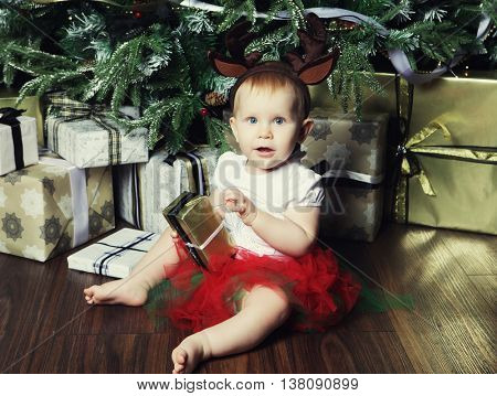 baby girl with the gift box near Decorating Christmas tree.