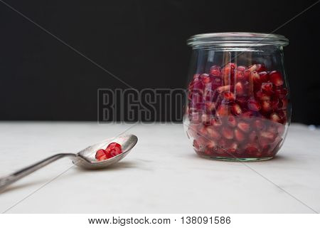 Front view of a glass container of pomegranate arils (seeds). A few seeds rest on a spoon.