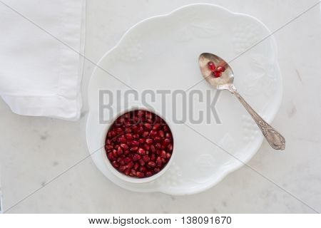 Top-down view of pomegranate seeds in a small bowl set on a dessert plate on white marble with napkin and silver sppon. Three arils (seeds) on spoon.