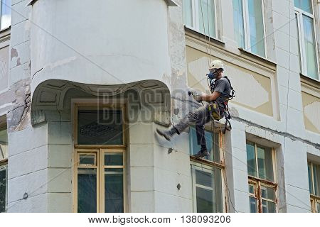 worker in a protective mask working with sander for smoothing wall surface of the building