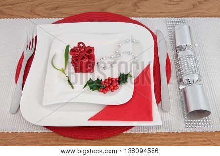 Christmas dinner decorative table setting with white porcelain plates, cutlery, serviette, holly, mistletoe, gift box decoration, silver cracker with diamond decoration over oak background.