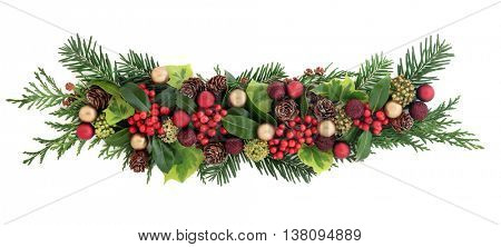 Christmas decoration with red and gold bauble decorations, holly and red berries, ivy, pine cones, cedar cypress  and fir leaf sprigs over white background.