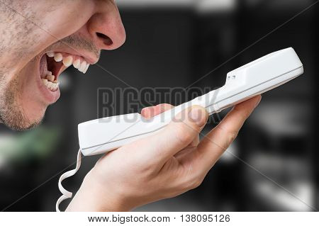 Angry man is yelling in phone in office.