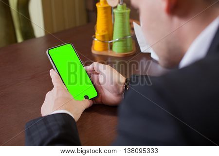 Side view shot of a man's hands using smart phone in interior rear view of business man hands busy using cell phone at office desk