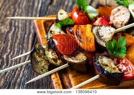 Fresh summer vegetable kebabs with eggplant and cherry tomatoes, charred veggie skewers on cutting board, veggies eating concept