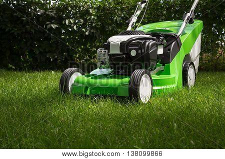 Outdoor shot of green lawnmower. Lawn mower