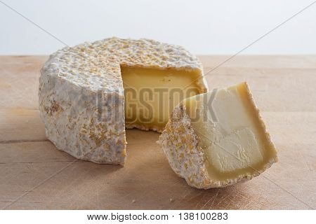Artisan cheese made of goat's milk on a wooden surface.