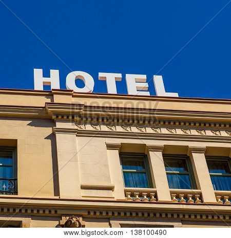 A modern hotel sign on building with classic arquitecture under a deep blue sky.