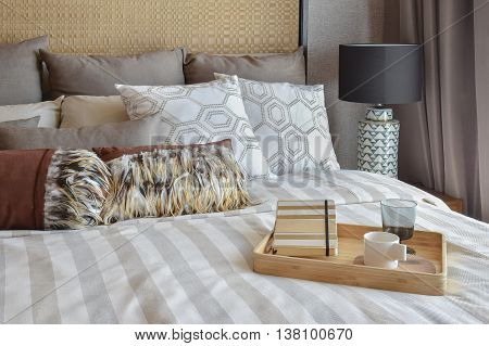 Stylish Bedroom Interior With Striped Pillows And Decorative Tea Set On Bed