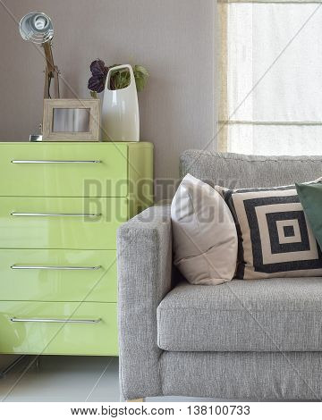 Cozy Sofa With Geometric Pattern Pillows And Green Sideboard In Living Corner
