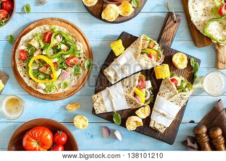 Tortilla wraps with grilled chicken fillet lager and grilled vegetables on a wooden table. Top view. Outdoors Food Concept