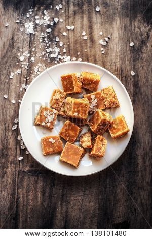Salted caramel pieces and sea salt close up. Butter caramel candy macro. Vintage rustic style