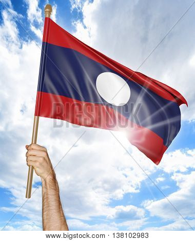 Person's hand holding the Laos national flag and waving it in the sky, 3D rendering