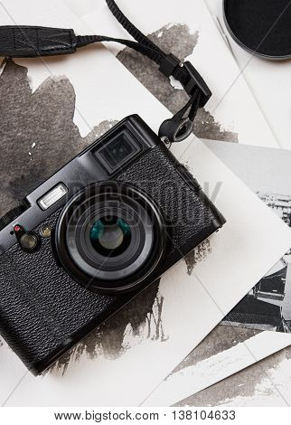 Retro camera and watercolor paintings on white table background, photographer artist workspace