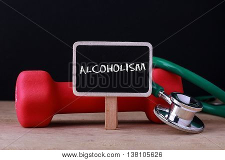 Medical concept - Stethoscope and dumbbell on wood with Alcoholism word