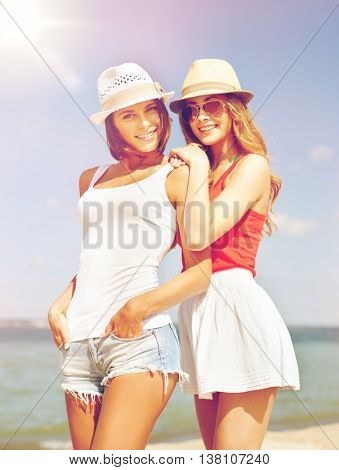 summer holidays and vacation concept - girls in hats on the beach