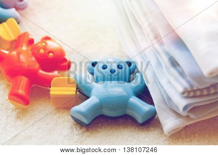 babyhood, childhood, toys, clothing and object concept - close up of baby rattle and clothes for newborn boy on towel